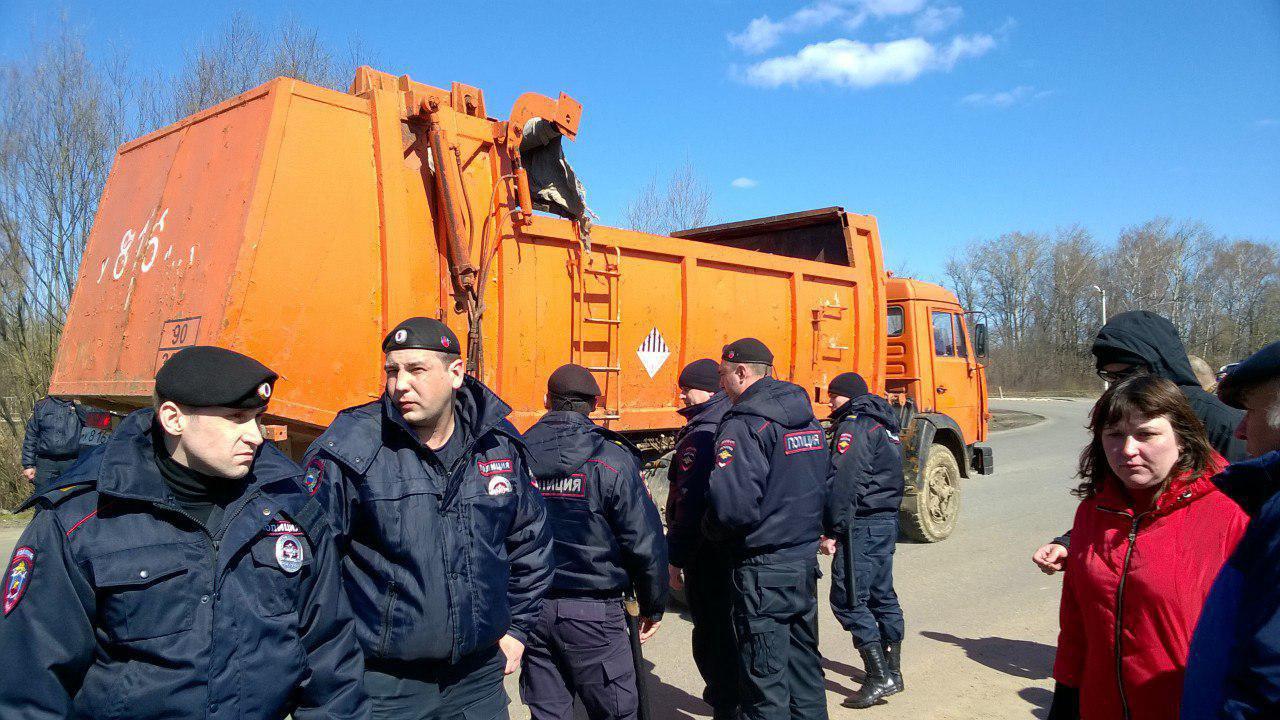 Сотрудники полиции перед мусоровозом / Фото: канал «Нет свалке в Коломне»